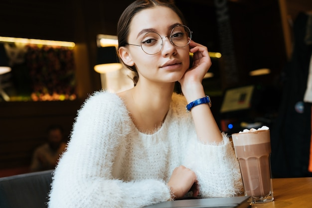 Uma bela jovem estudante de óculos sentada em um café, na mesa está um cappuccino