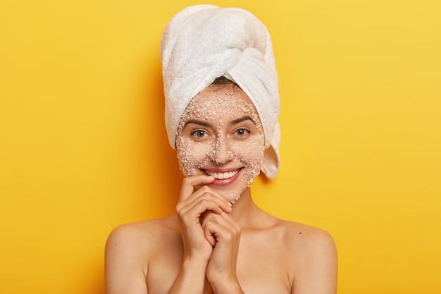 Uma bela jovem europeia gosta de tratamentos de beleza, sorri suavemente, mantém o dedo perto dos lábios, olha, aplica esfoliante de sal marinho para esfoliar a pele