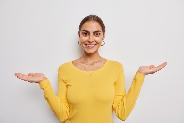 Uma bela jovem europeia sorri, levanta as palmas das mãos, espalha as mãos sobre a parede branca, demonstra que algo usa um macacão amarelo casual fingindo estar segurando algo