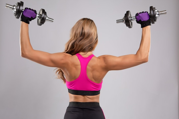 Uma bela jovem faz exercícios com halteres nos músculos das costas.