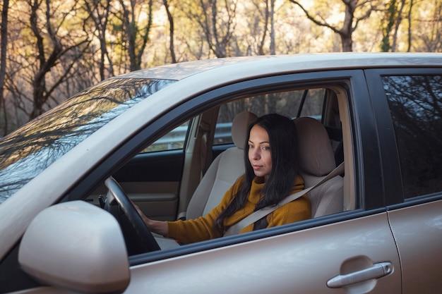 Uma bela jovem feliz dirigindo seu carro na floresta. a ideia e o conceito de viagem e descoberta, fall getaway