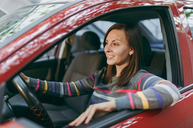 Uma bela jovem feliz e sorridente mulher europeia de cabelos castanhos com pele limpa e saudável, vestida com uma camiseta listrada, senta-se em seu carro vermelho com interior preto. viajar e dirigir o conceito.