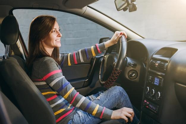 Uma bela jovem feliz sorridente europeia de cabelos castanhos com pele limpa e saudável, vestida com uma camiseta listrada, senta-se em seu carro com interior preto. viajar e dirigir o conceito.