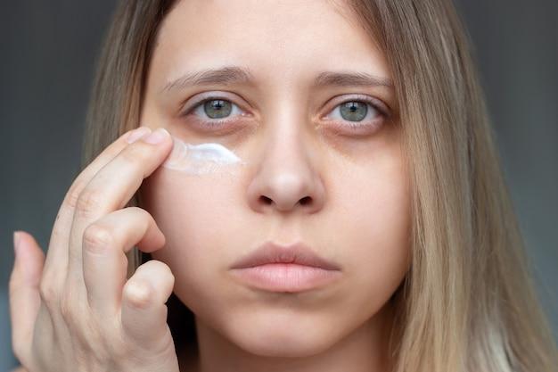 Uma bela jovem loira caucasiana toca a pele do rosto enquanto aplica o creme para olhos roxos.