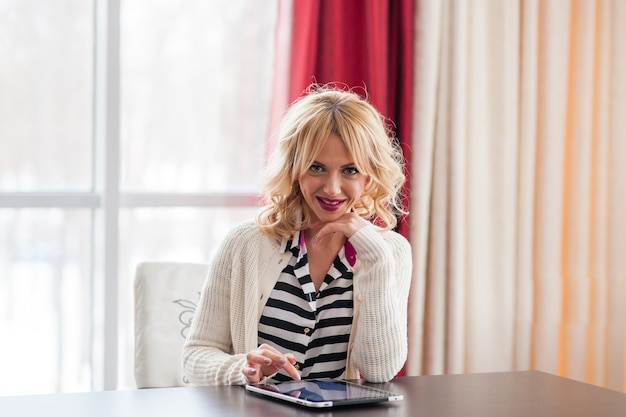 Uma bela jovem loira sentada à mesa usando um laptop.