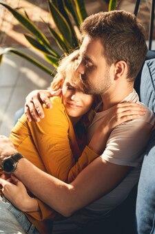 Uma bela jovem loira sorridente e um homem caucasiano sereno cochilando pacificamente no sofá