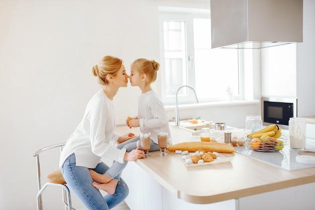 Uma bela jovem mãe com cabelo claro em renda branca e calça jeans azul sentado em casa