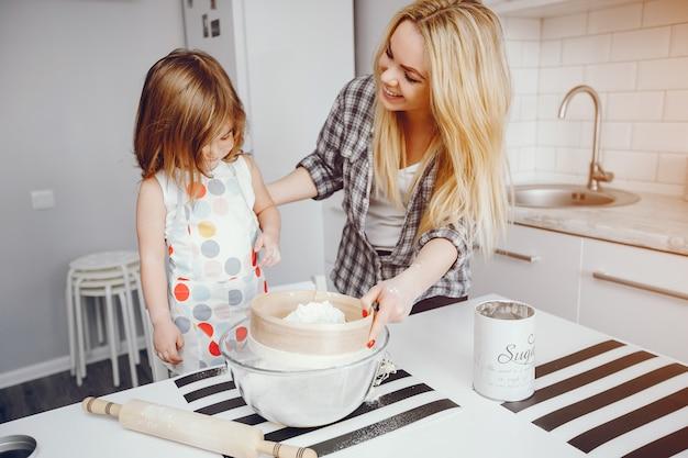 Uma bela jovem mãe com sua filha está cozinhando na cozinha em casa