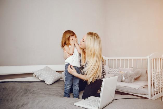 Uma bela jovem mãe com sua filha jogando em casa