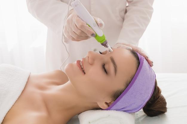 Uma bela jovem no consultório de cosmetologistas recebe mesoterapia fracionada para o rosto