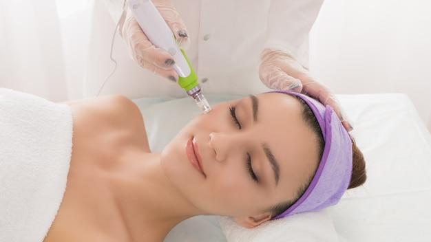 Uma bela jovem no escritório do cosmetologista recebe mesoterapia fracionada para o rosto.