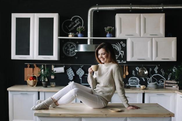 Uma bela jovem no interior da cozinha moderna