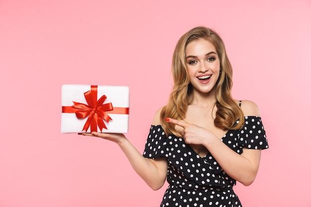 Uma bela jovem posando isolada na parede rosa segurando uma caixa de presente