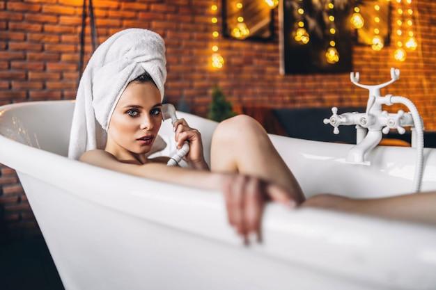 Uma bela jovem posando. mulher deitada em uma banheira branca com uma toalha na cabeça. uma parede de tijolo vermelho com guirlandas amarelas