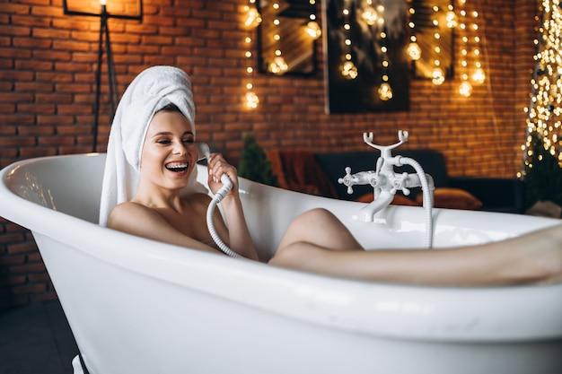 Uma bela jovem posando no estúdio. mulher deitada em uma banheira branca com uma toalha na cabeça.