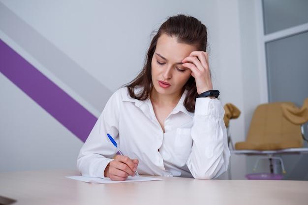 Uma bela jovem se senta à mesa e assina documentos importantes.