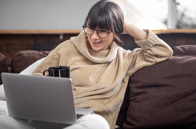 Uma bela jovem se senta no sofá em casa com um copo de bebida e olha alegremente para a tela do computador.