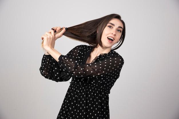 Uma bela jovem segurando seu cabelo saudável e brilhante.