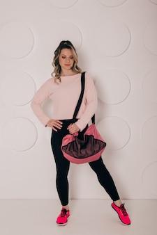 Uma bela jovem segurando uma sacola esportiva olhando para a câmera