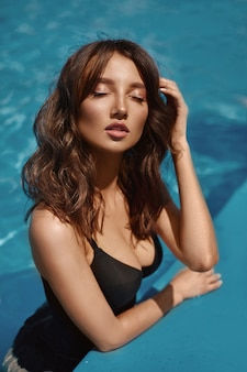 Uma bela jovem sensual com cabelo preto e corpo perfeito vestindo um elegante maiô relaxando na piscina da luxuosa villa.