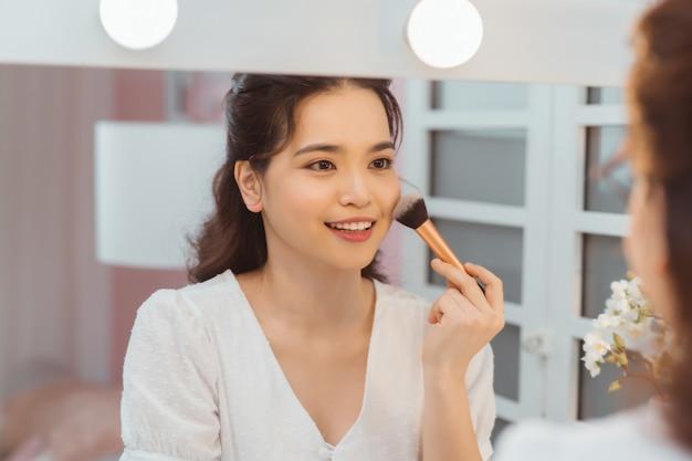 Uma bela jovem sentada em uma mesa de maquiagem e fazendo a maquiagem.