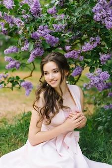 Uma bela jovem sorridente com maquiagem profissional em um delicado vestido rosa senta-se perto de um arbusto de flor lilás