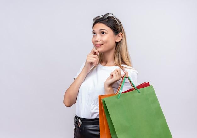 Uma bela jovem sorridente com uma camiseta branca e óculos de sol na cabeça, pensando enquanto segura sacolas de compras na parede branca