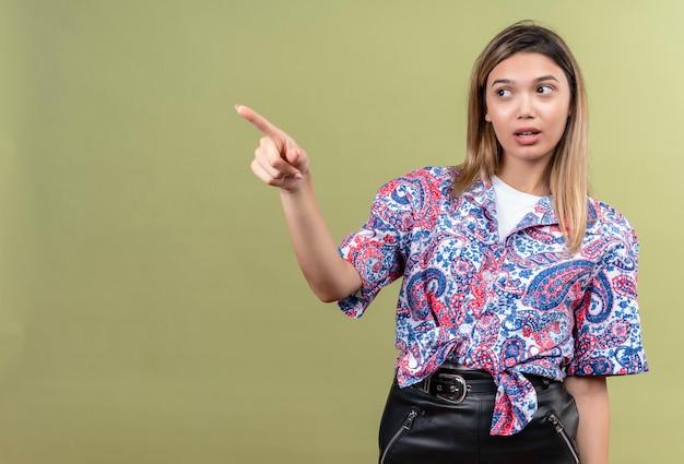 Uma bela jovem vestindo uma camisa com estampa paisley apontando com o dedo indicador e olhando de lado em uma parede verde