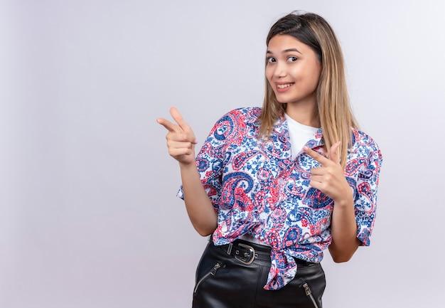 Uma bela jovem vestindo uma camisa com estampa paisley apontando com o dedo indicador enquanto olha para uma parede branca