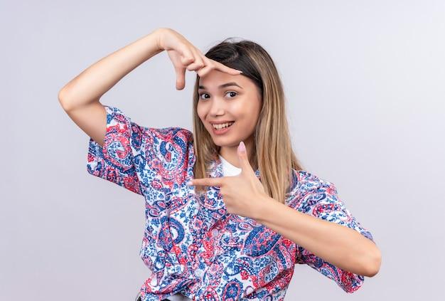 Uma bela jovem vestindo uma camisa estampada de paisley fazendo uma moldura com as mãos e os dedos com uma cara feliz enquanto olha para uma parede branca