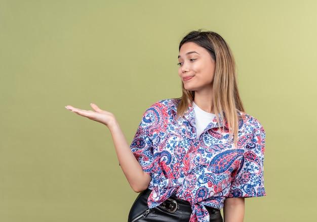 Uma bela jovem vestindo uma camisa estampada de paisley levantando a mão e olhando para ela na parede verde