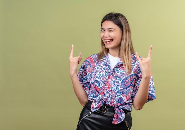 Uma bela jovem vestindo uma camisa estampada de paisley mostrando um gesto de pedra com as mãos