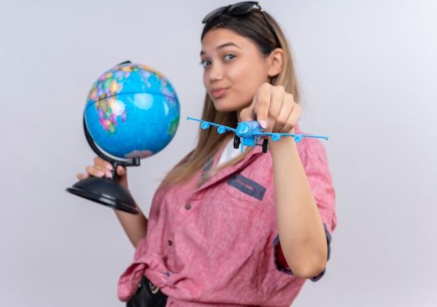 Uma bela jovem vestindo uma camisa vermelha com óculos escuros segurando um globo enquanto pilotava um avião de brinquedo azul em uma parede branca