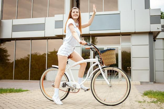 Uma bela jovem viaja para a cidade de bicicleta. alugue e alugue transporte para o dia. garota feliz anda de bicicleta. estilo de vida esportivo acenando com a mão