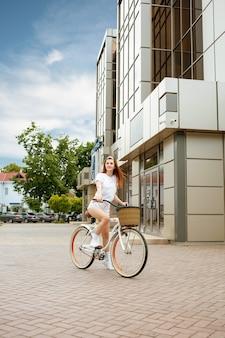 Uma bela jovem viaja para a cidade de bicicleta. alugue e alugue transporte para o dia. garota feliz anda de bicicleta. estilo de vida esportivo verão, primavera