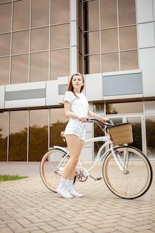 Uma bela jovem viaja para a cidade de bicicleta. alugue e alugue transporte para o dia. garota feliz anda de bicicleta. estilo de vida esportivo