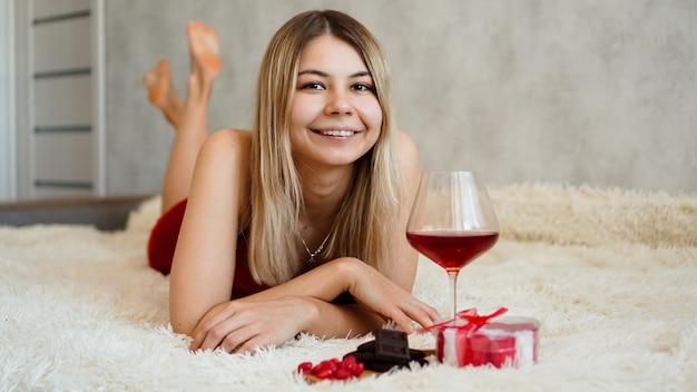 Uma bela loira sorridente está deitada na cama. dia dos namorados de manhã. uma taça de vinho, chocolate, doces e um presente ao lado da menina. feliz manhã apaixonada