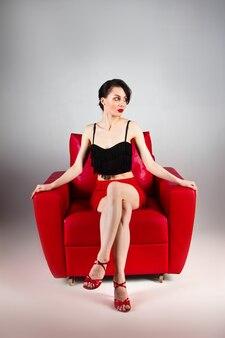 Uma bela morena com sapatos vermelhos se senta em uma poltrona vermelha sobre um fundo cinza.