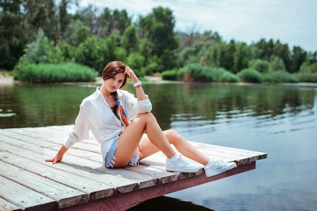 Uma bela morena em uma camisa branca e shorts jeans senta-se em uma ponte de madeira. o conceito de viagens e caminhadas.