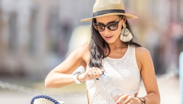 Uma bela mulher abre uma garrafa de água mineral pura durante um dia quente de verão.