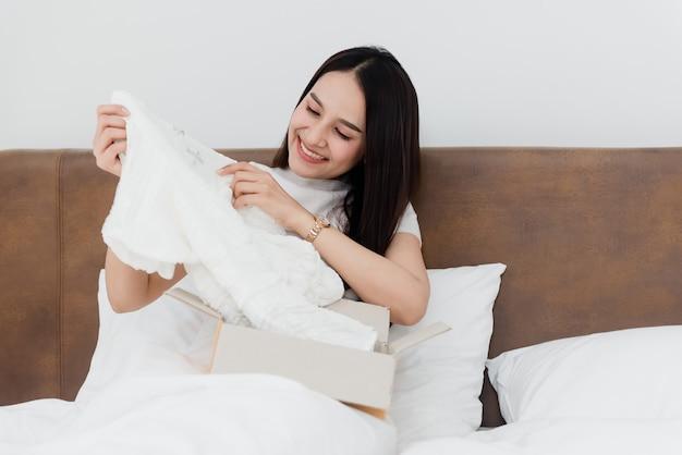 Uma bela mulher asiática está olhando para as roupas escolhidas na caixa de papel no quarto branco.