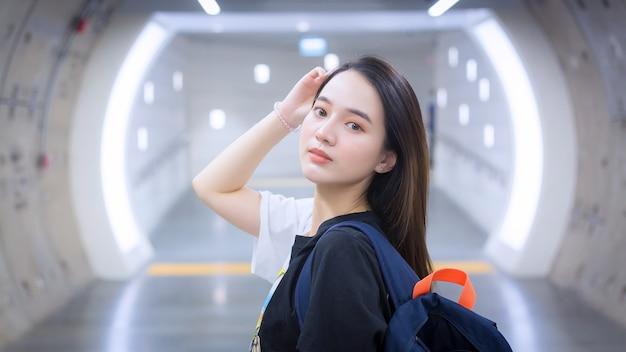 Uma bela mulher asiática vestindo uma camisa preta sorriu ao entrar no túnel do metrô.