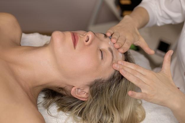 Uma bela mulher caucasiana de 35 anos recebendo procedimento de tratamento de spa na clínica