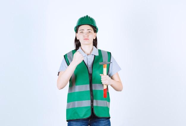 Uma bela mulher com uma camisa de jaqueta verde mostra sua força e o martelo na frente da parede cinza
