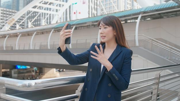 Uma bela mulher de negócios asiática está fazendo videochamada com colegas ou familiares na cidade moderna, cooperação empresarial e conceito de tecnologia de negócios.