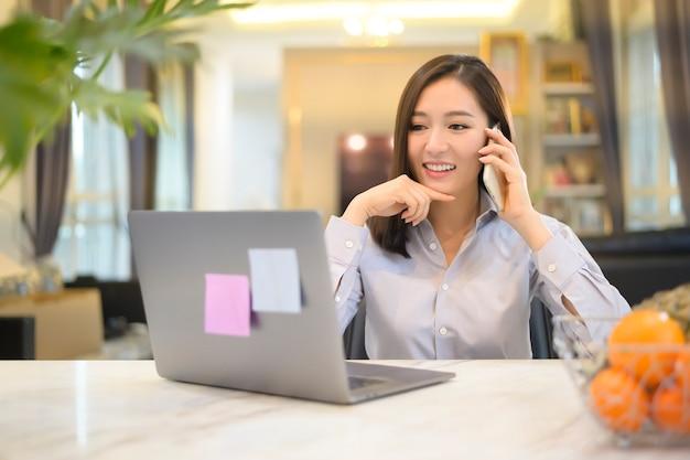 Uma bela mulher de negócios asiáticos está trabalhando com seu computador em casa, telecomunicações, distanciamento social, conceito de trabalho em casa.