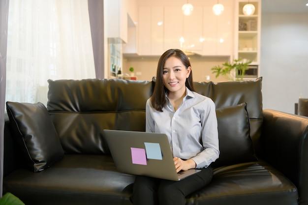 Uma bela mulher de negócios asiáticos está trabalhando com seu computador em casa.