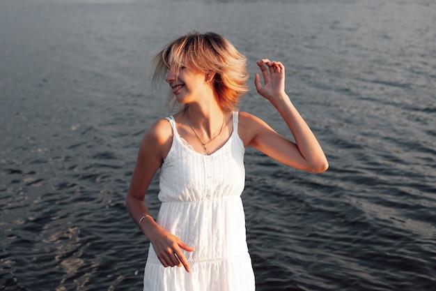 Uma bela mulher de perfil no contexto da água uma foto romântica de um jovem sorriso feliz ...