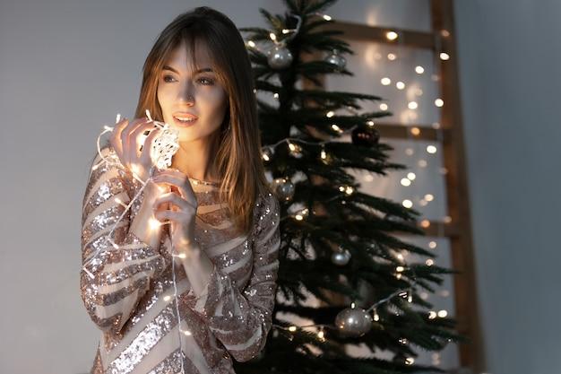 Uma bela mulher em um vestido festivo se levanta, sorri e segura uma guirlanda luminosa nas mãos perto do rosto. luz abafada. árvore de natal minimalista e escadas ao fundo. foco suave.