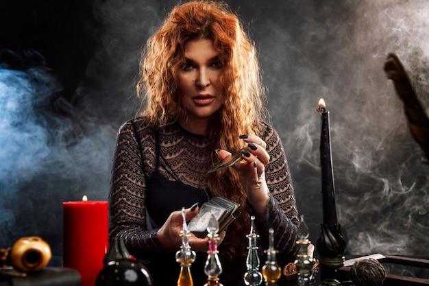 Uma bela mulher idosa realiza um ritual mágico com velas e embaralha um baralho de cartas de tarô